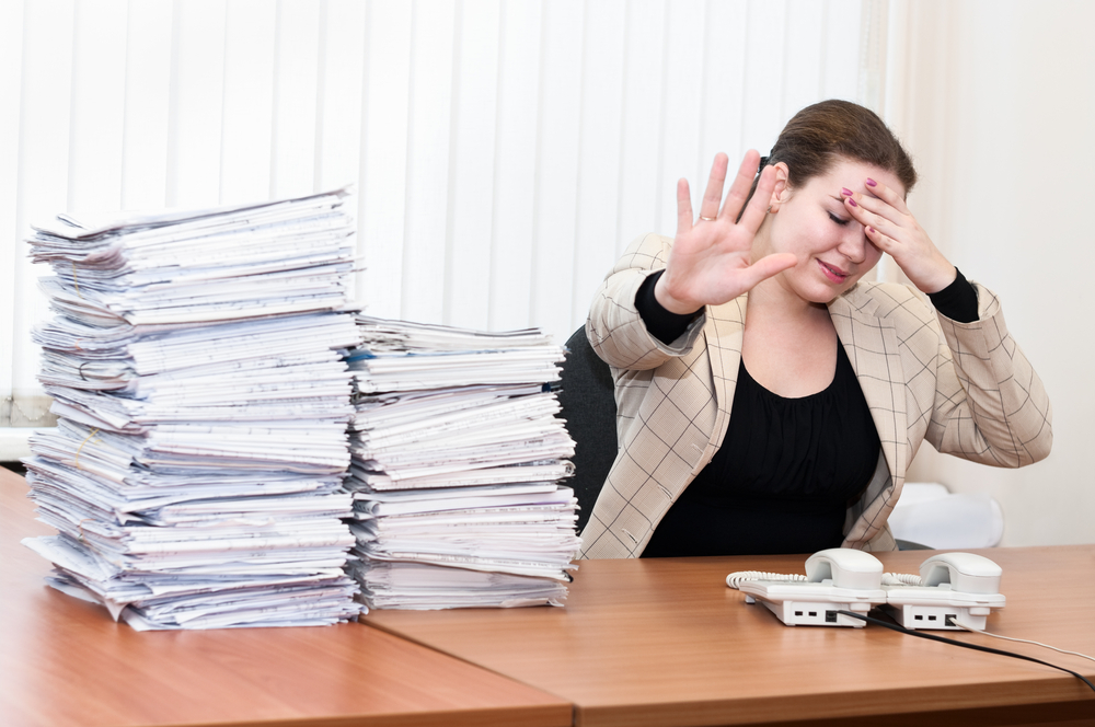 papers pile up on woman's desk