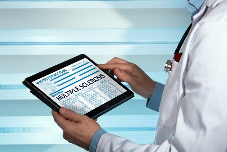 doctor-reading-about-multiple-sclerosis-on-tablet