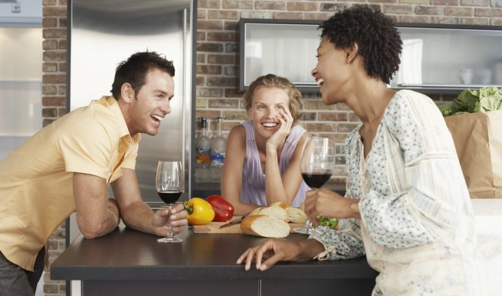 friends drinking in kitchen during party