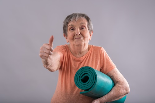 Happy elderly woman with yoga mat