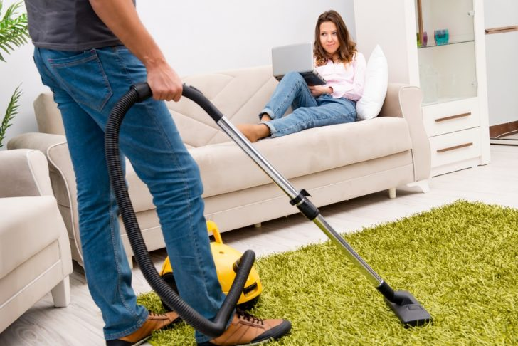 husband vacuuming while wife is on sofa