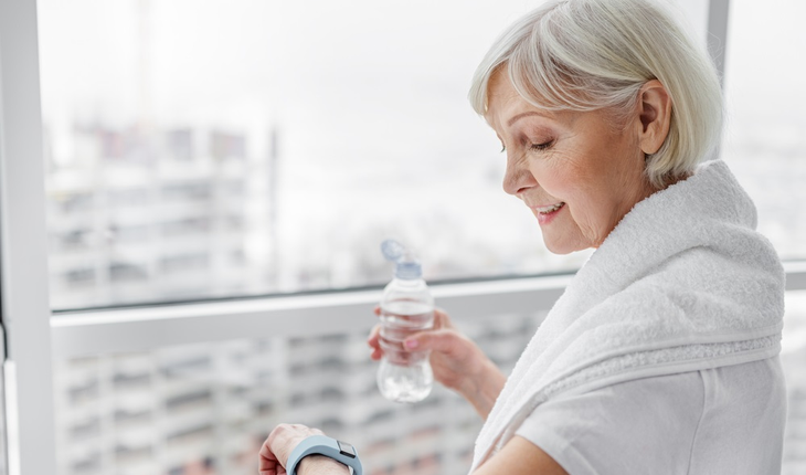 Mature woman drinking water in gym