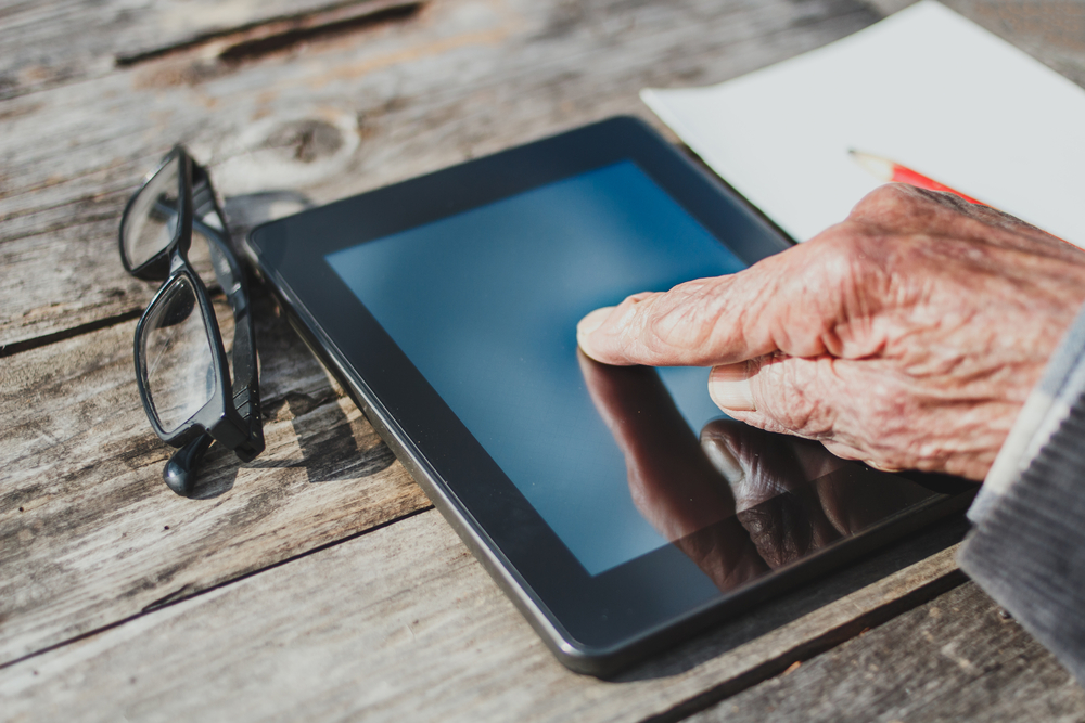 Older hand on tablet deice