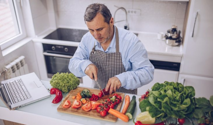 older man and healthy food in kitchen