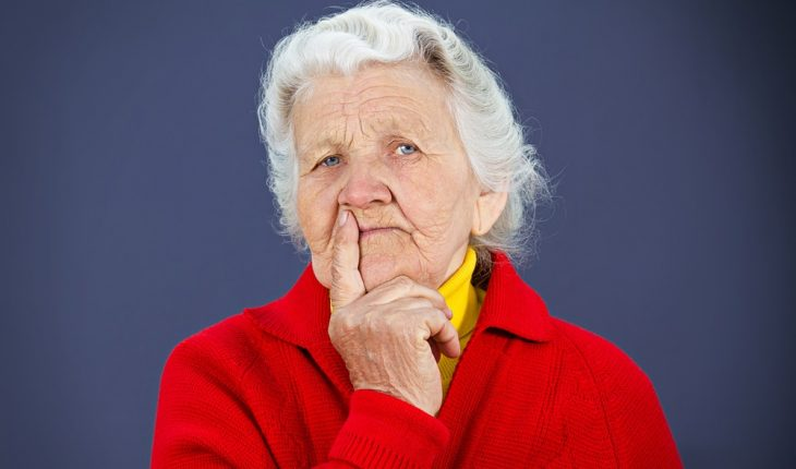 older woman, puzzled, red sweater