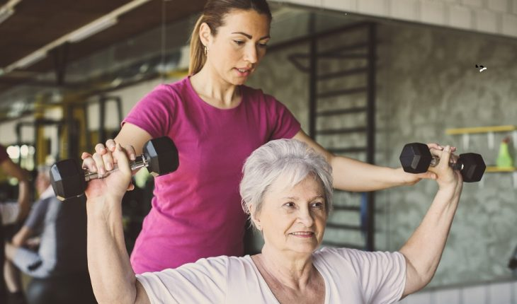 older woman lilflting weights with trainer