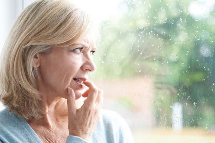 sad middle-aged woman looking out of window