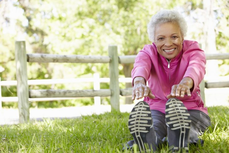 senior-woman-stretching-in-park