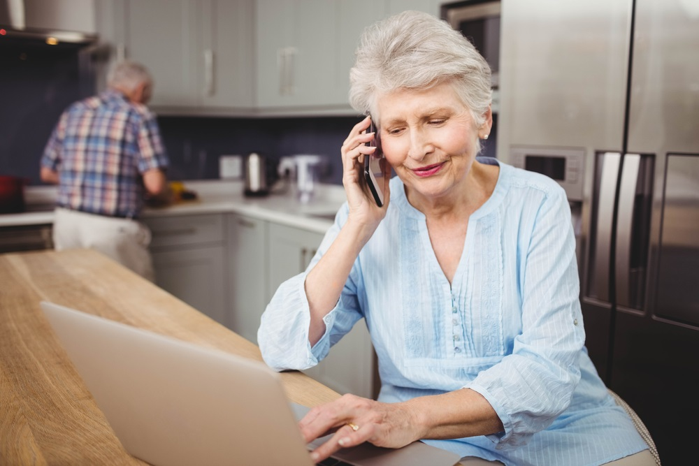 senior-woman-in-kitchen-with-laptop
