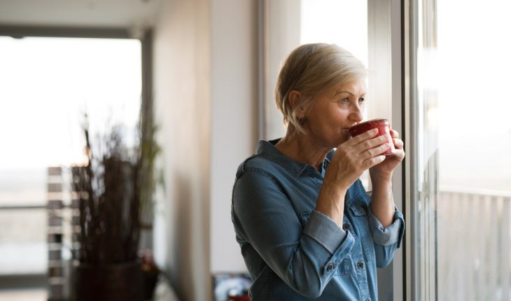 senior-woman-looking-out-window-with-coffee