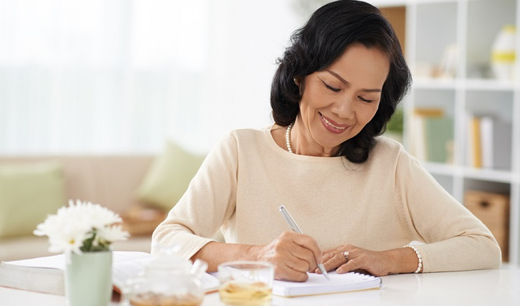 smiling-mature-woman-writing