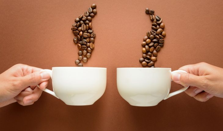Two hands with coffee cups and beans