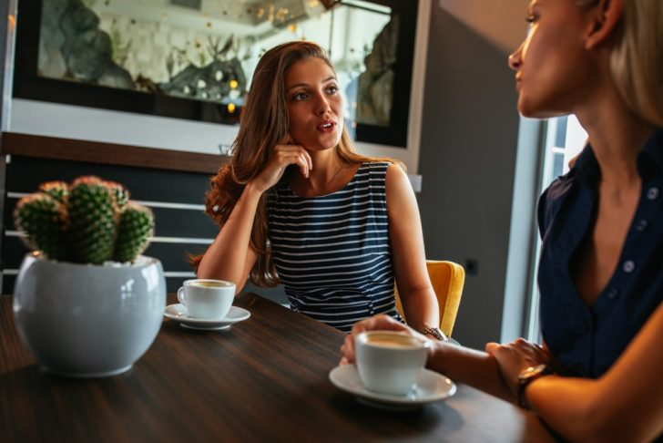 two-young-women-talking-in-cafe