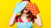 Woman hiding face behind oven mits