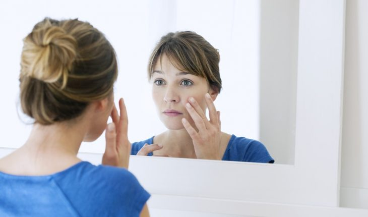 woman-looking-at-skin-in-mirror