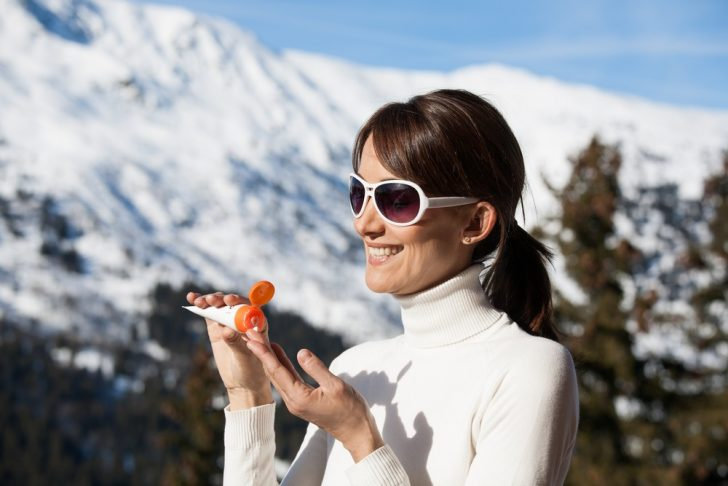woman-putting-on-sunscreen-in-winter