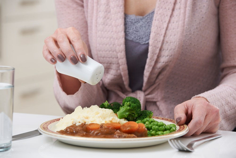 woman-sprinkling-salt-on-meal