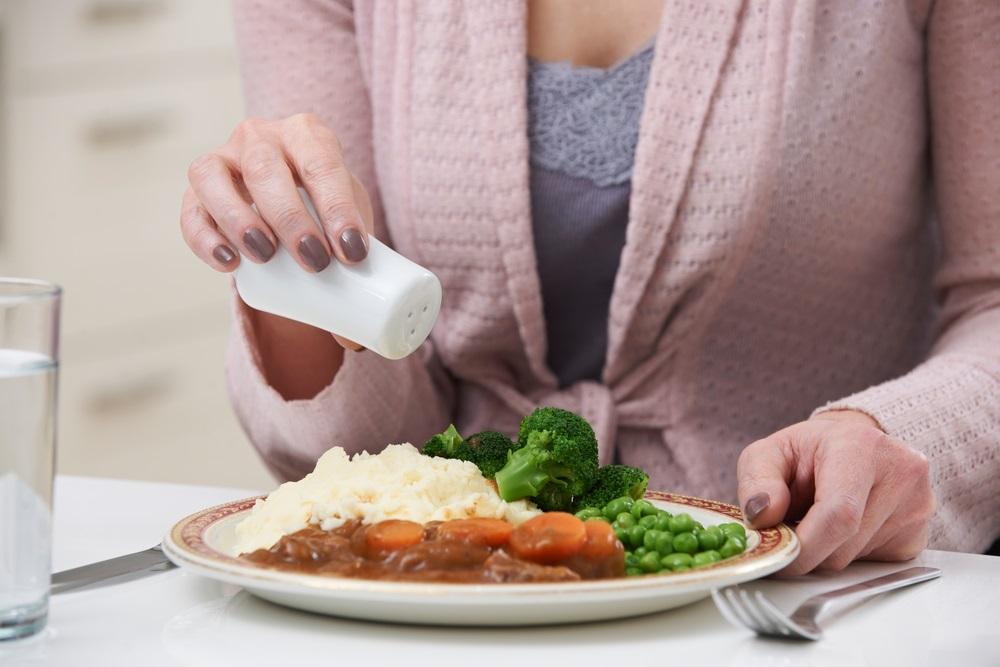woman-sprinkling-salt-on-meal