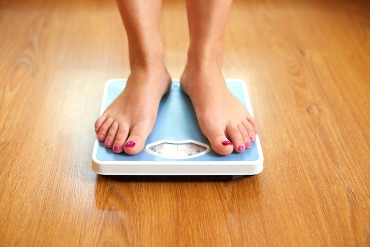 Woman standing on weight loss scale