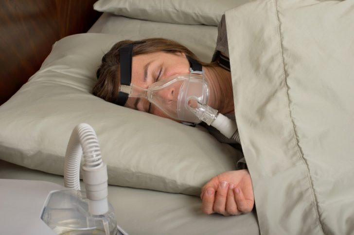 woman sleeping with CPAP machine