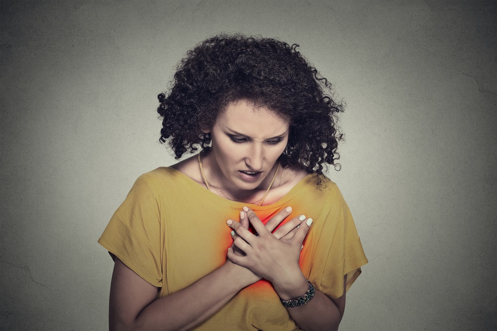 Woman with hand on chest heart disease