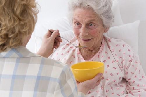 caregiver feeding elderly woman