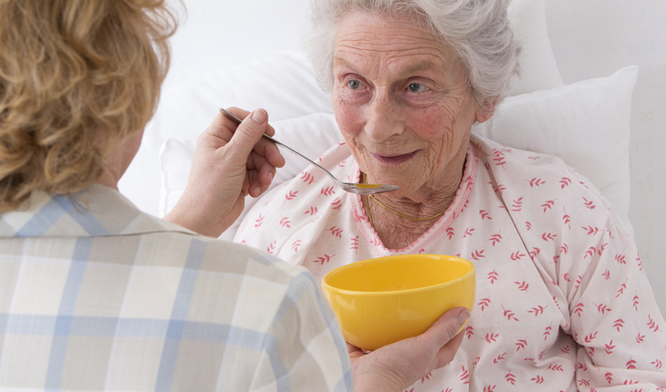 caregiver feeding elderly woman