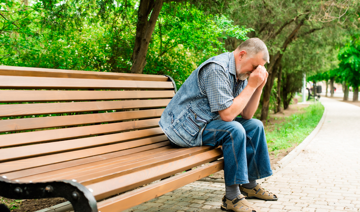 depressed older man on park bench