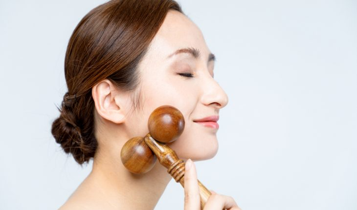 facial massage roller, woman using one