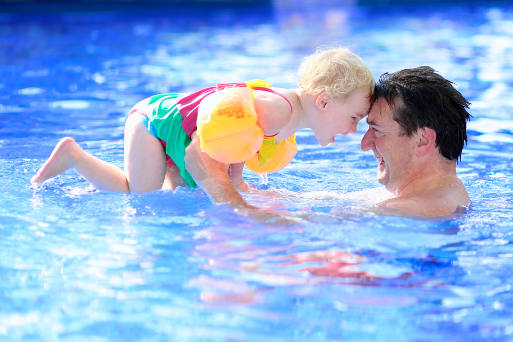father and child in swimming pool