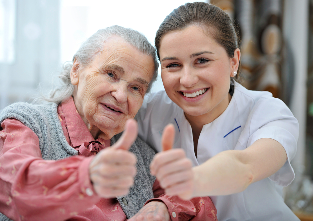frail elderly with nurse, thumbs up.jpg