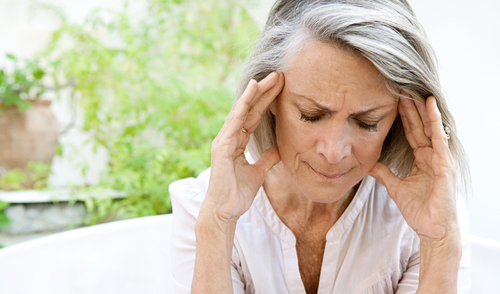 mature woman holding head with headache