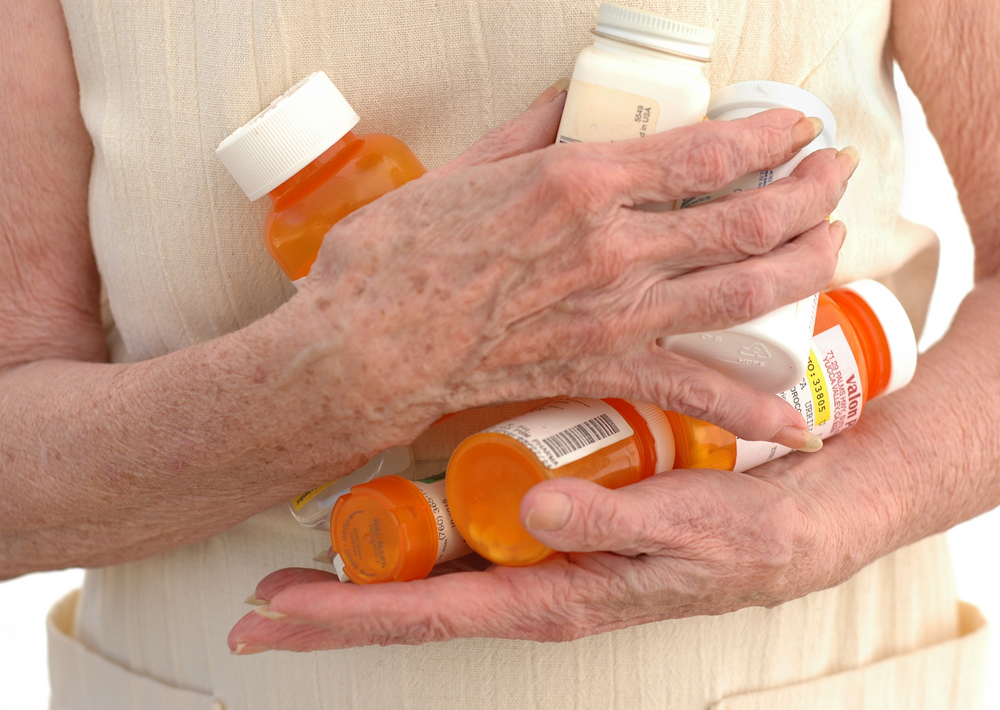 The hands of a senior woman clutching many meds.