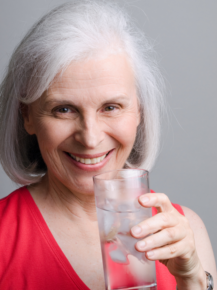 mature woman drinking a glass of water.jpg