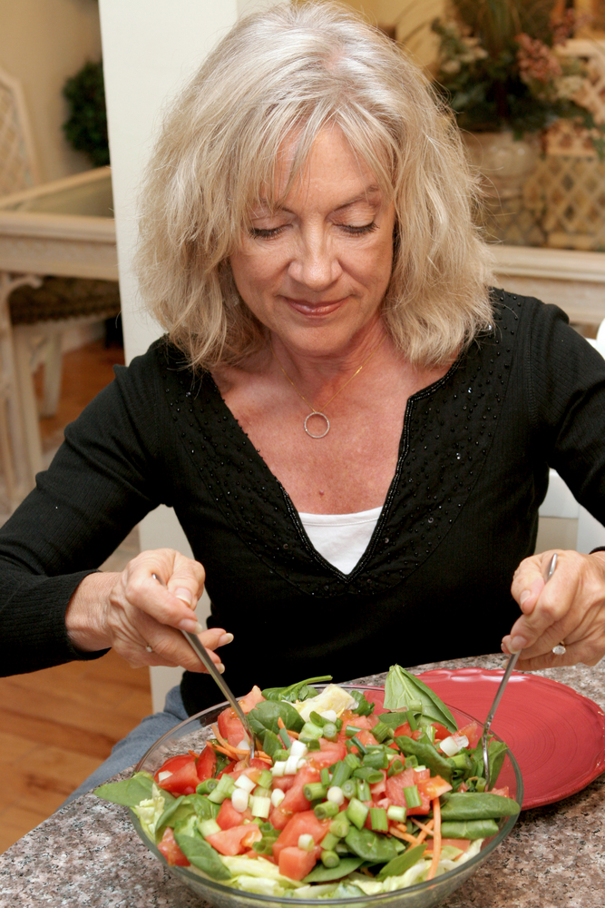 mature woman eating a salad.jpg
