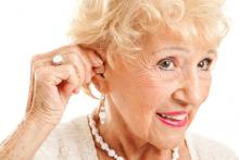 mature woman inserts hearing aid.jpg