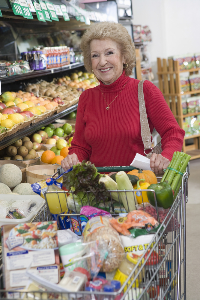mature woman with full grocery cart.jpg