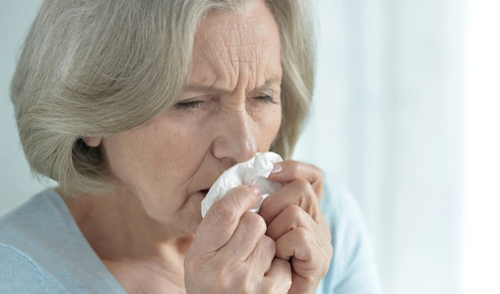 mature woman sneezing