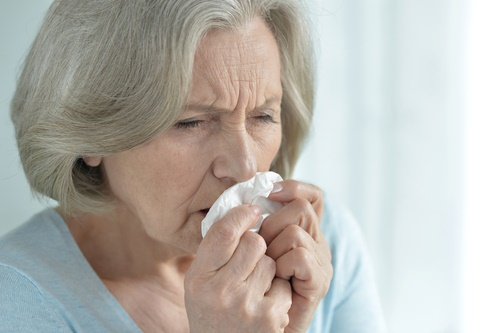 mature woman sneezing