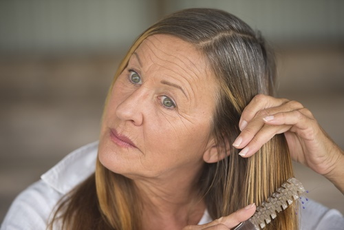 mature woman styling hair