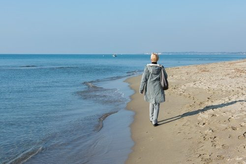 mature woman walking on beach in winter