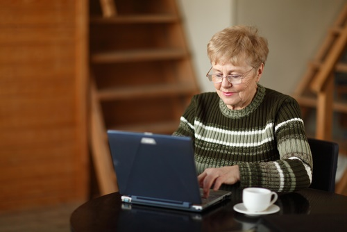 mature woman writing on computer
