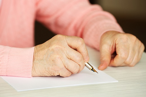 mature woman writing on paper
