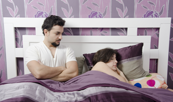 couple in bed - man looks annoyed