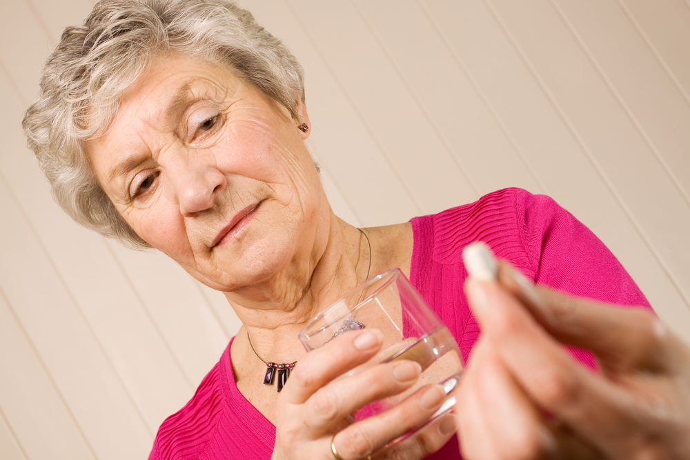 older woman with pill and water glass.jpg