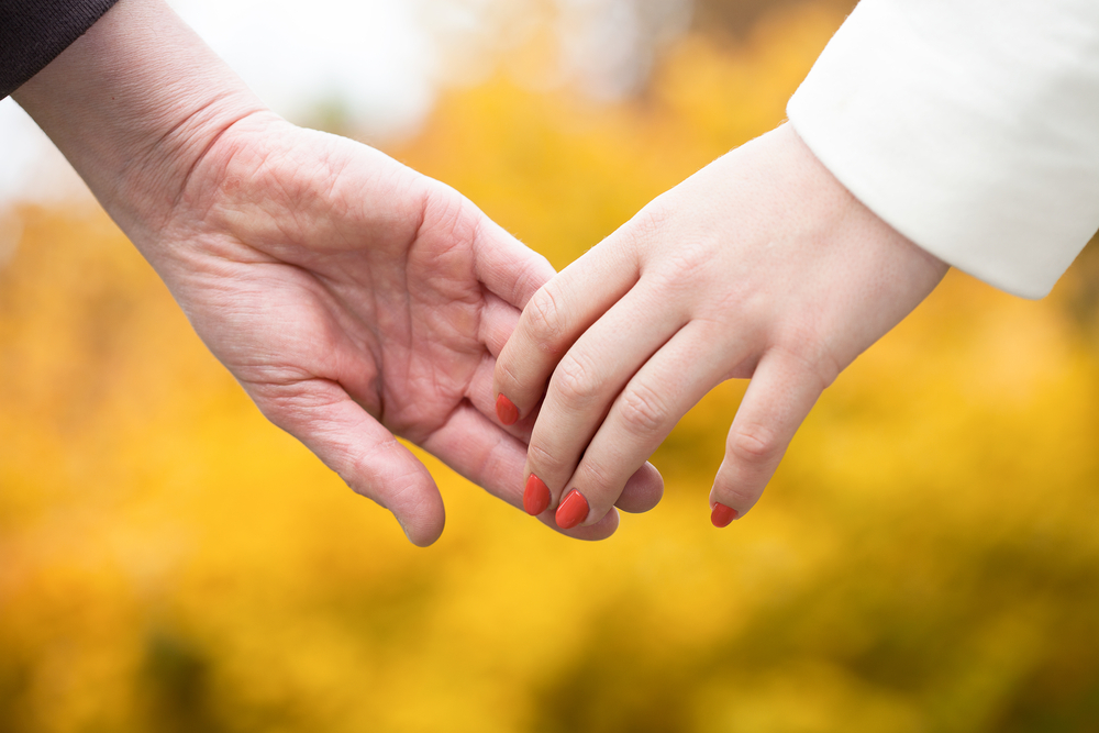 older couple holding hands, no rings