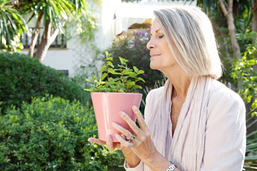 older woman smelling a plant