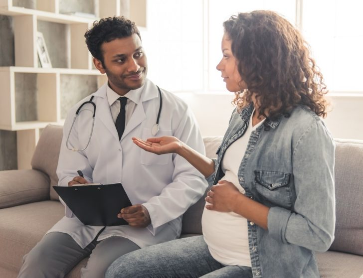 pregnant woman talking with her doctor