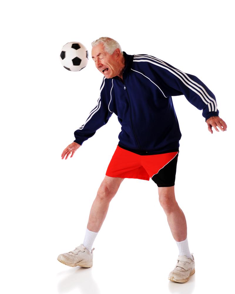 senior heading soccer ball