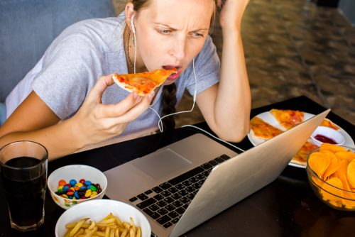 woman unhealthy eating by her laptop